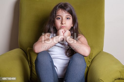 Unhappy small beautiful middle eastern girl with white t-shirt and black hairs looking at camera.