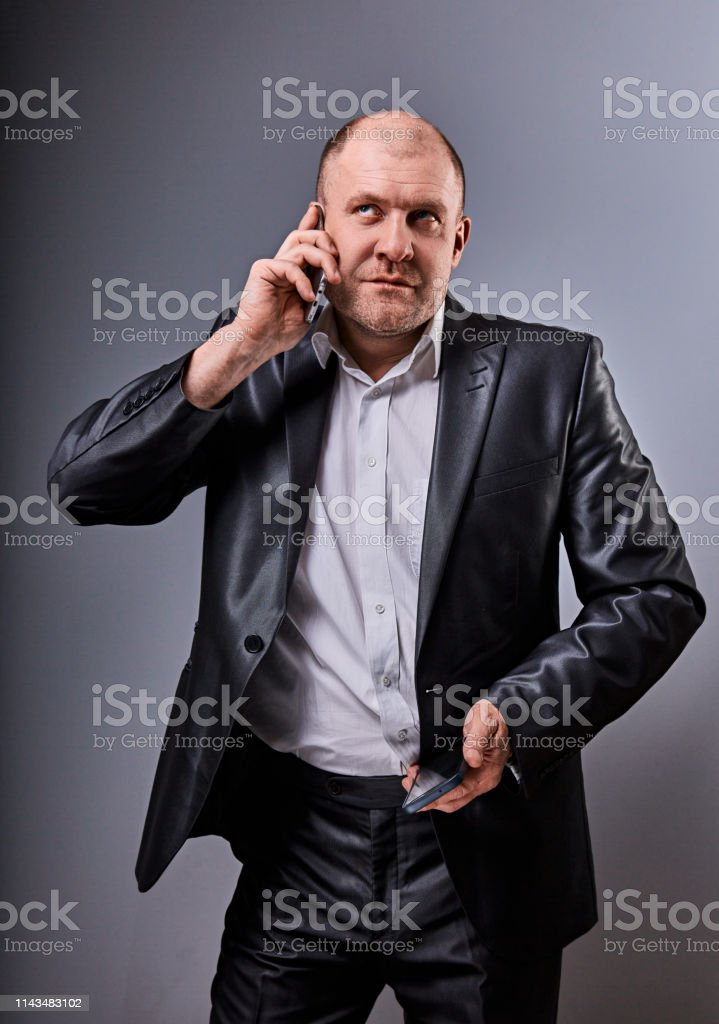 Unhappy stressed angry business man talking on mobile phone very emotional in office suit and looking up on grey studio background. Closeup royalty-free stock photo