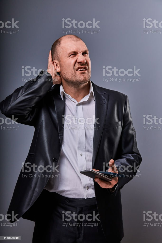 Unhappy stressed tired business man holding two mobile phones in hands and looking up in office suit on grey studio background. Closeup royalty-free stock photo