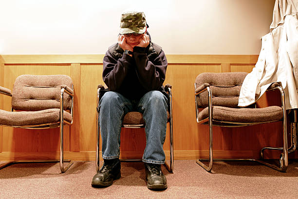 XL unhappy teen boy unhappy teen boy sits outside of high school principal's office (XL) absentee stock pictures, royalty-free photos & images