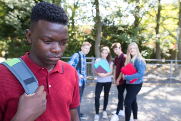 unglückliche teenager wird durch schulfreunde über geplaudert - vorurteil stock-fotos und bilder