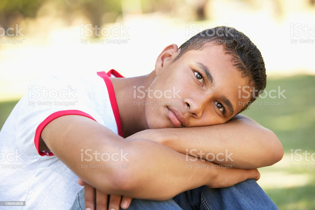Unhappy Teenage Boy Sitting In Park stock photo