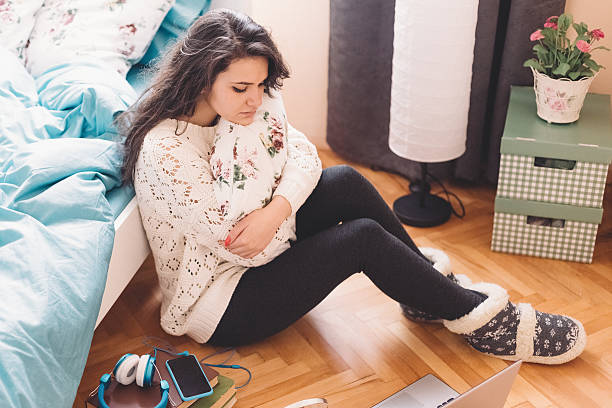 Unhappy teenage girl at home Young girl sitting thoughtfuly on the floor girl bedroom stock pictures, royalty-free photos & images