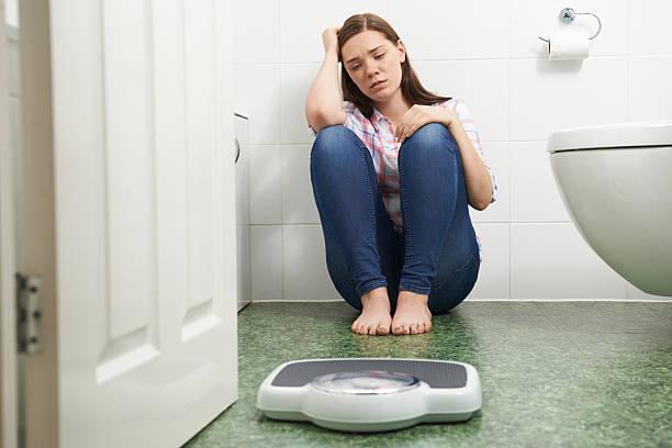 unhappy teenage girl sitting on floor looking at bathroom scales - lichaamsbewustzijn stockfoto's en -beelden