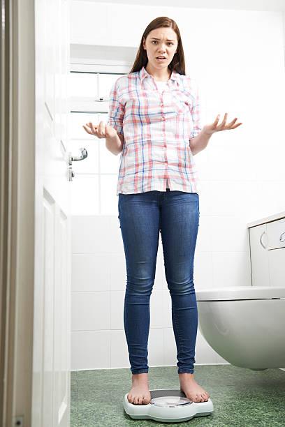 Descontente adolescente de pé na balança de banheiro - foto de acervo