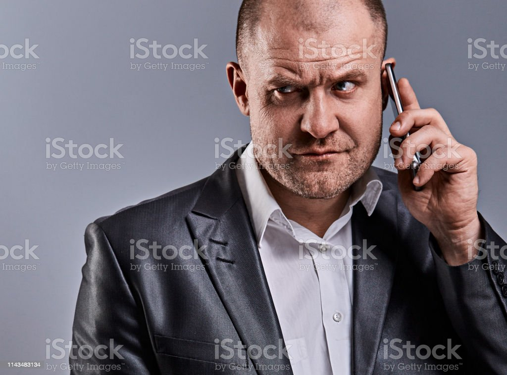 Unhappy tired angry business man talking on mobile phone and holding in hand one more phone in office suit on grey studio background. Closeup royalty-free stock photo