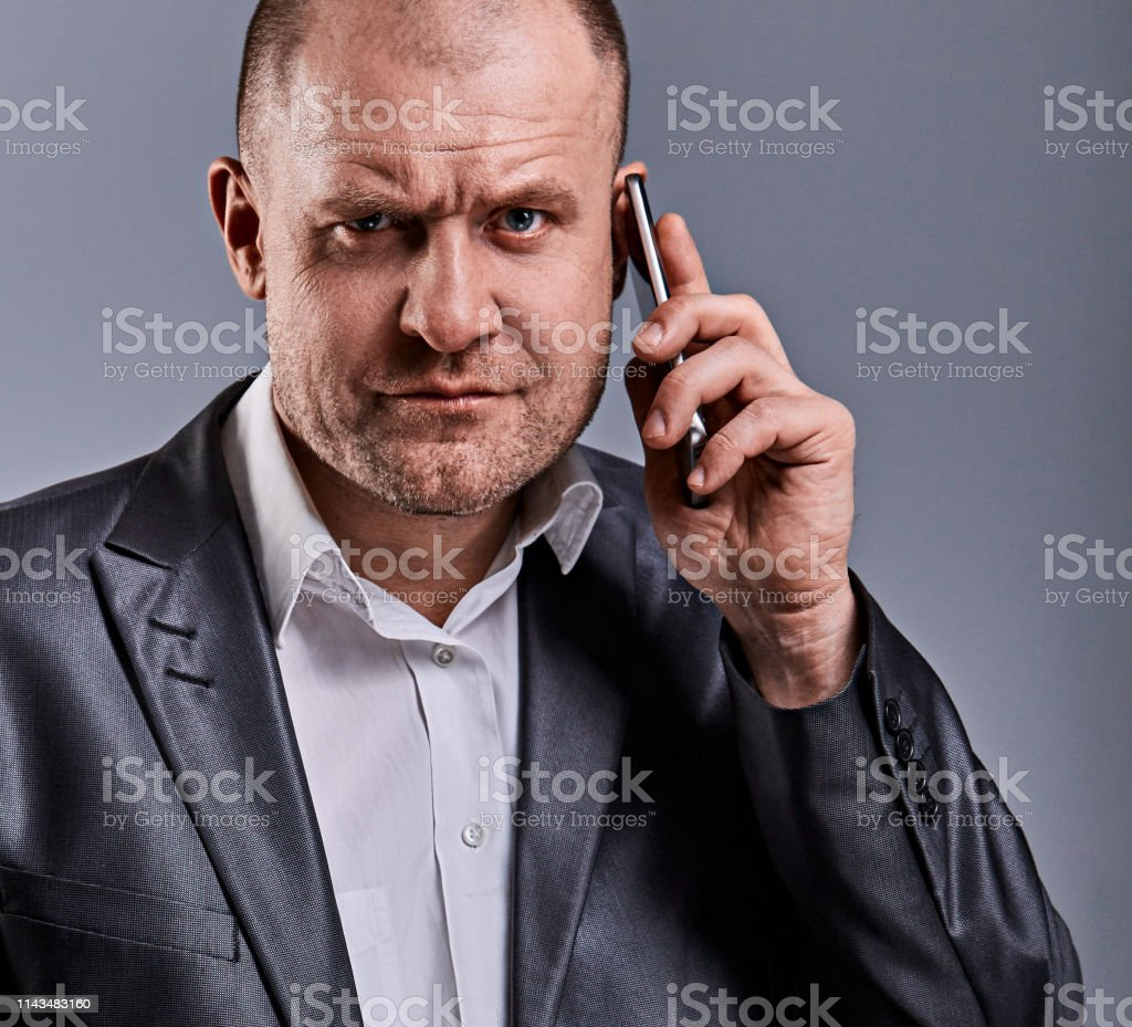 Unhappy tired angry business man talking on mobile phone and holding in hand one more phone in office suit on grey studio background. toned face portrait royalty-free stock photo
