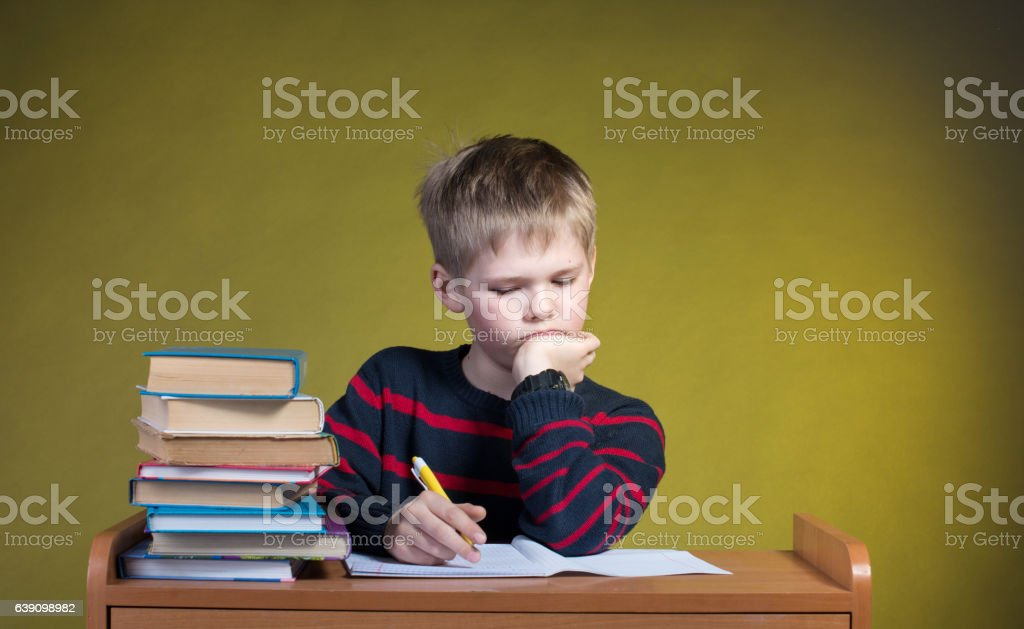 Unhappy Tired Little Boy Doing His Homework. Boring School Studies. stock photo