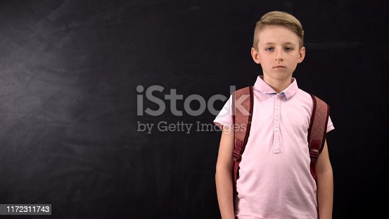 istock Unhappy tired schoolboy standing near chalkboard, suffering overload at school 1172311743