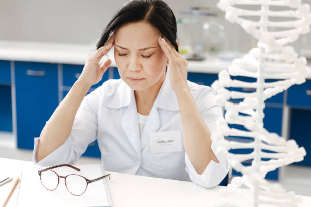 Unhappy tired woman suffering from the headache Unpleasant pain. Unhappy tired pleasant woman sitting at the table and holding her temples while having a headache dna purification stock pictures, royalty-free photos & images