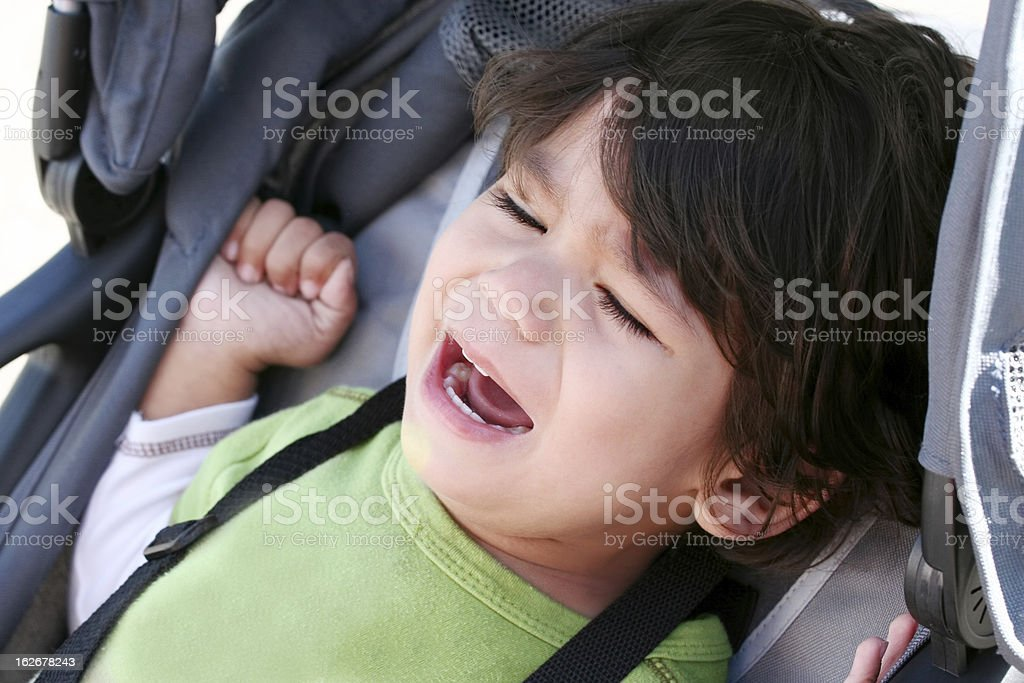 Unhappy toddler crying in stroller stock photo