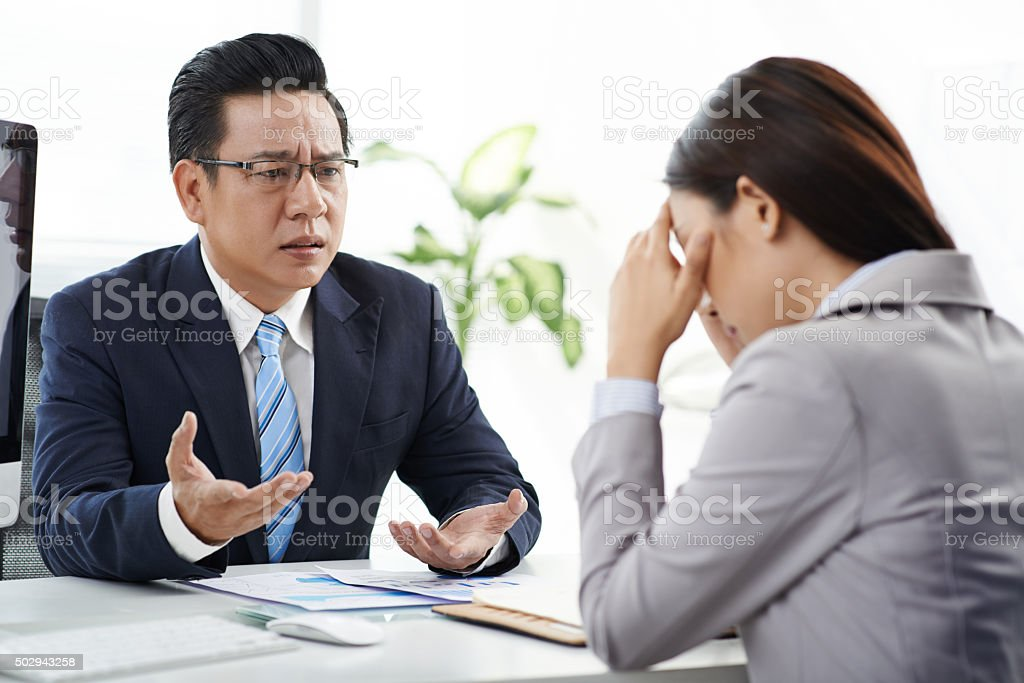 Unhappy with work of assistant stock photo