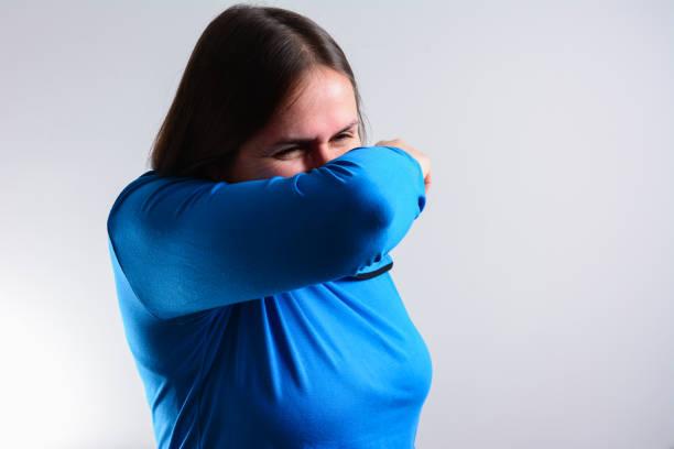 olycklig kvinna hosta in i armbågen, inte hennes hand.  hosta råd från experter som försöker minimera risken för viral överföring koncept - mature woman fever on white bildbanksfoton och bilder