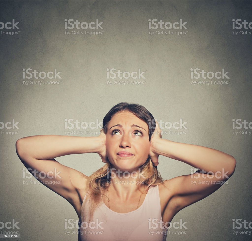 unhappy woman covering ears looking up stop making loud noise stock photo