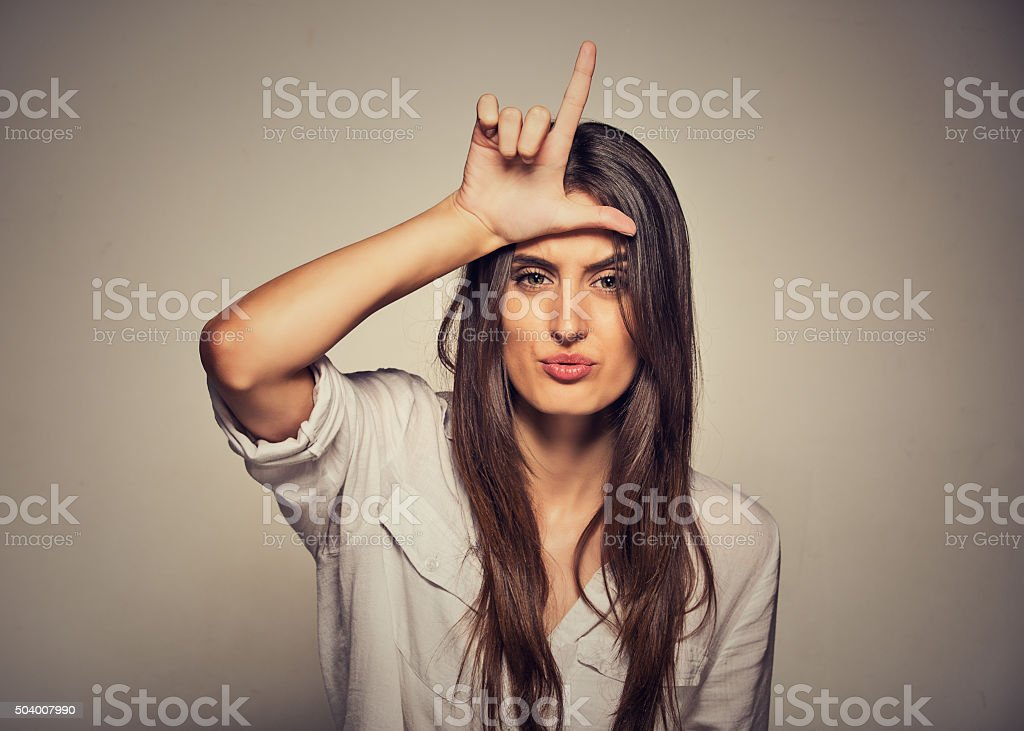 unhappy woman giving loser sign on forehead, looking with disgust stock photo