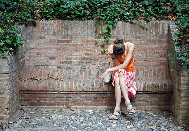 unhappy woman in orange dress sitting on the stony bench - young singles stock photos and pictures