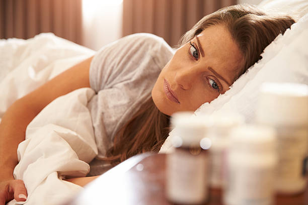 unhappy woman looking at medication on bedside table - sleeping pill stock photos and pictures