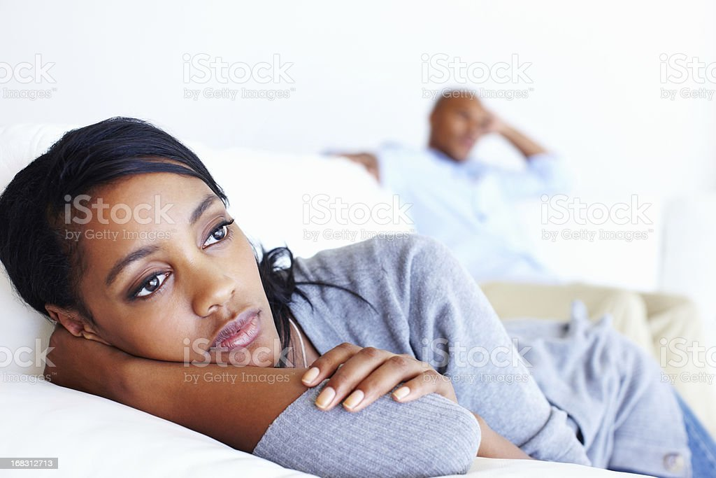 Unhappy woman lying in couch stock photo
