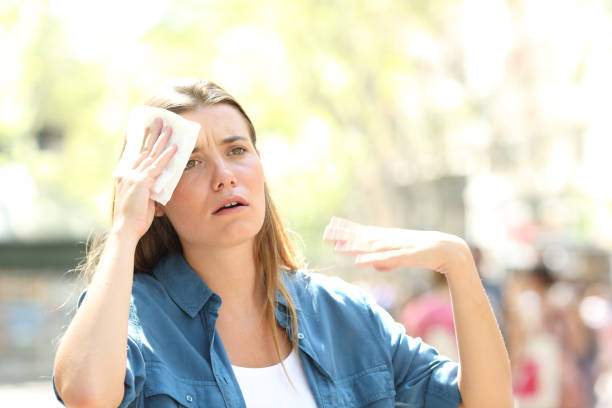 Unhappy woman sweating suffering a heat stroke stock photo