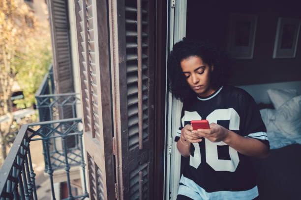 Unhappy woman texting at the balcony Depressed woman at home text messaging central europe stock pictures, royalty-free photos & images