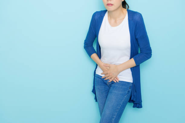 unhappy woman using hands touching belly position stock photo