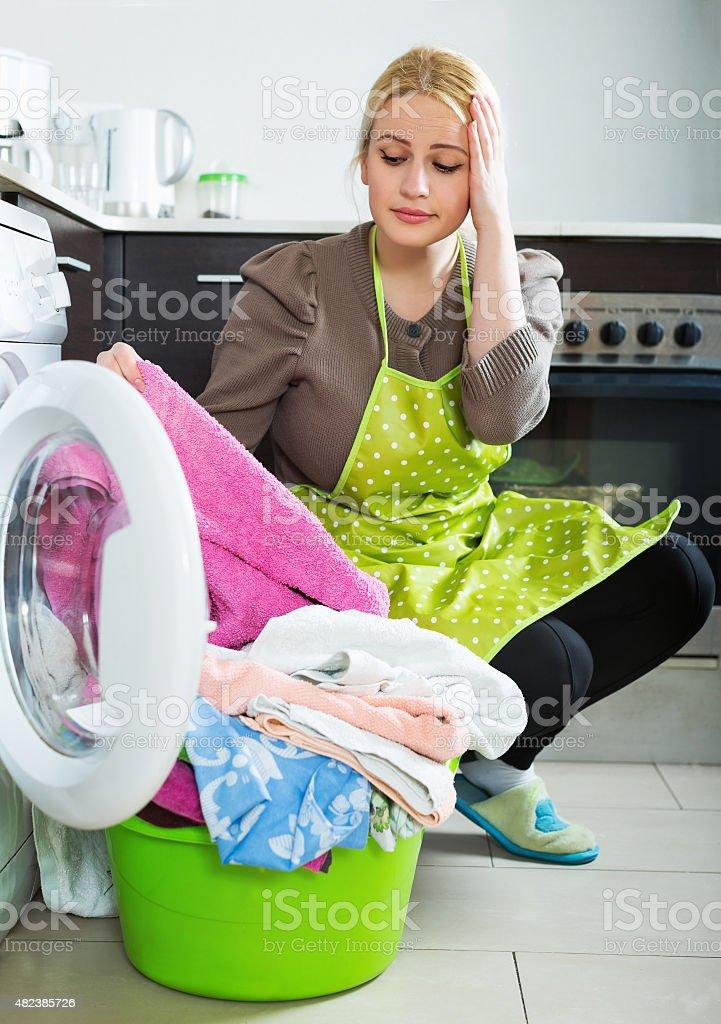 Unhappy woman using washing machine stock photo