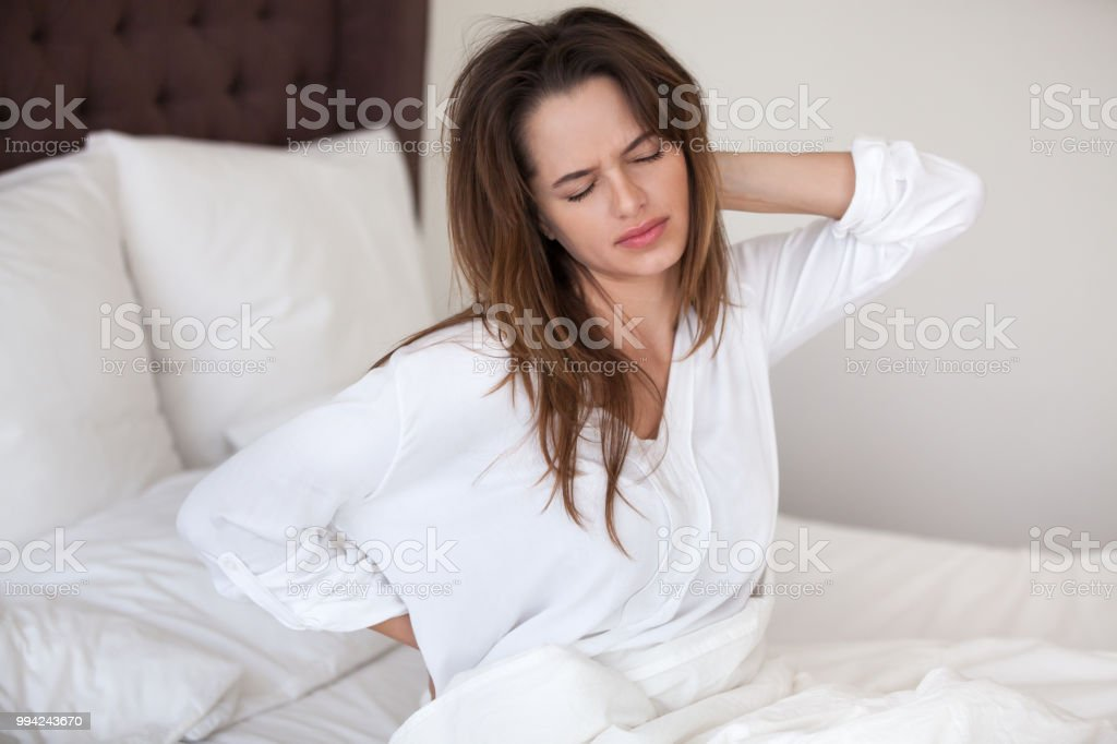 Unhappy woman waking up in bed feeling neck back pain stock photo