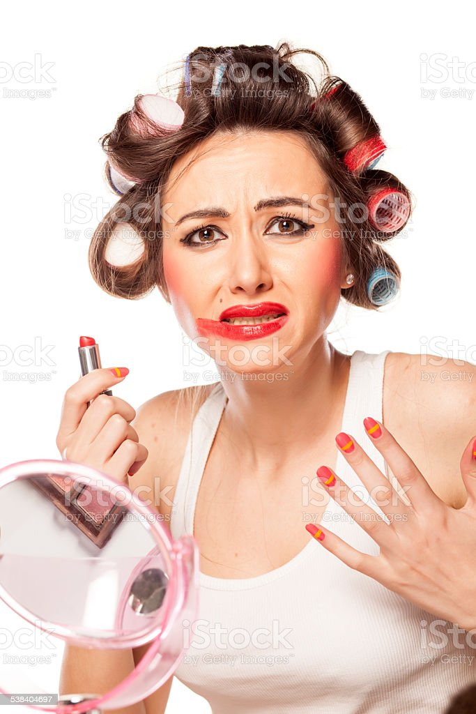 Unhappy woman with curlers posing with smeared makeup stock photo