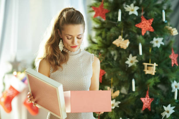 unhappy woman with opened Christmas gift near Christmas tree unhappy young woman with opened Christmas present box near Christmas tree shock tactics stock pictures, royalty-free photos & images