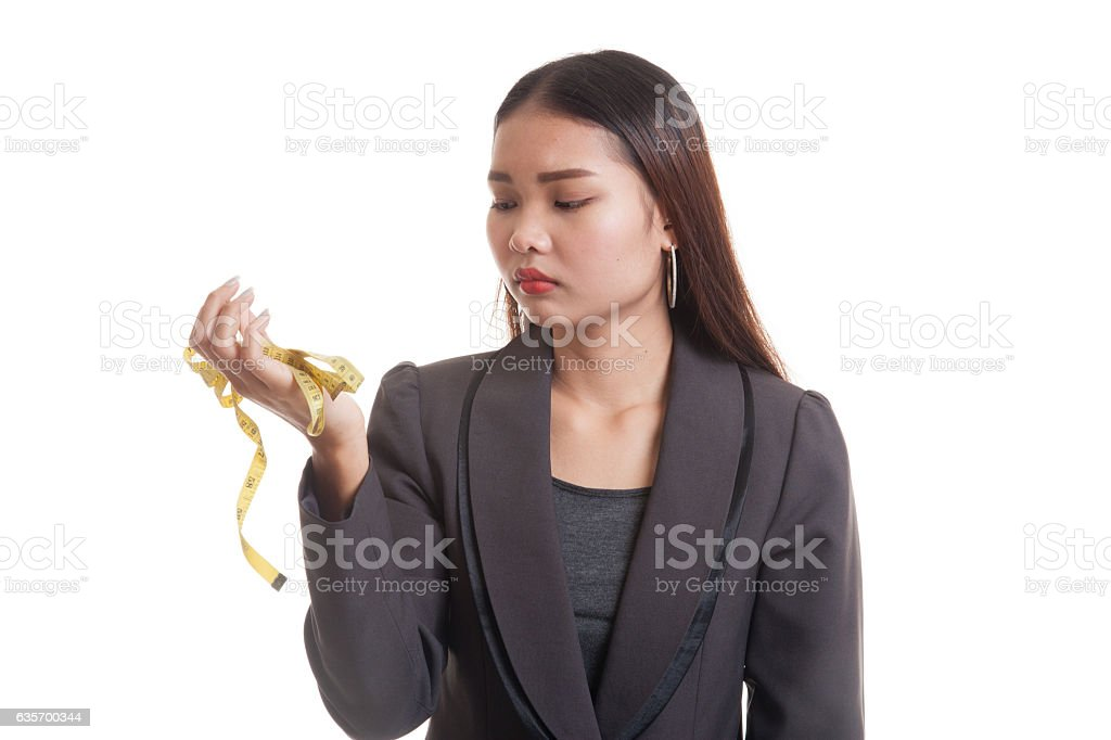 Unhappy young Asian business woman with measuring tape. royalty-free stock photo