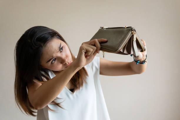 Unhappy young asian woman open her empty wallet Unhappy young asian woman open her empty wallet empty wallet stock pictures, royalty-free photos & images