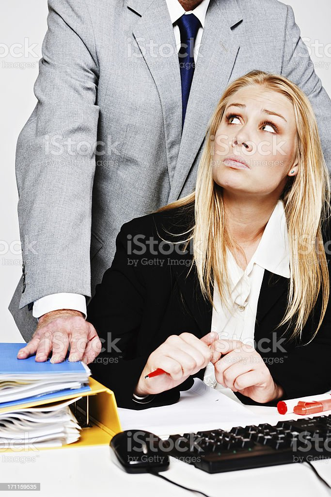 Unhappy young businesswoman looks over shoulder at harassing businessman stock photo
