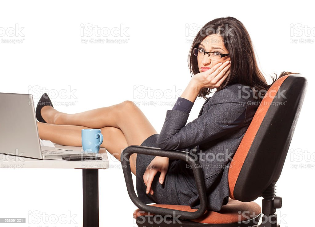 Unhappy young businesswoman with her legs on the table stock photo