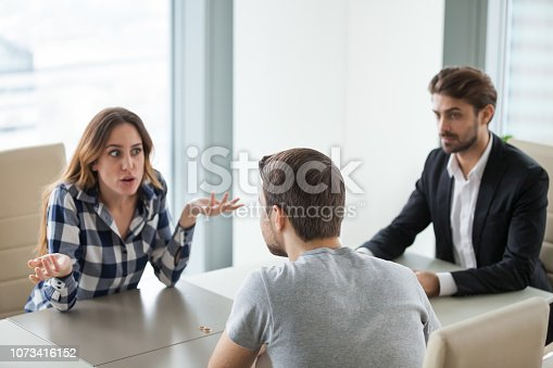 istock Unhappy young couple at meeting with lawyer about divorce 1073416152