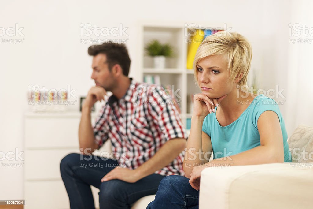 Unhappy young couple sitting in living room royalty-free stock photo
