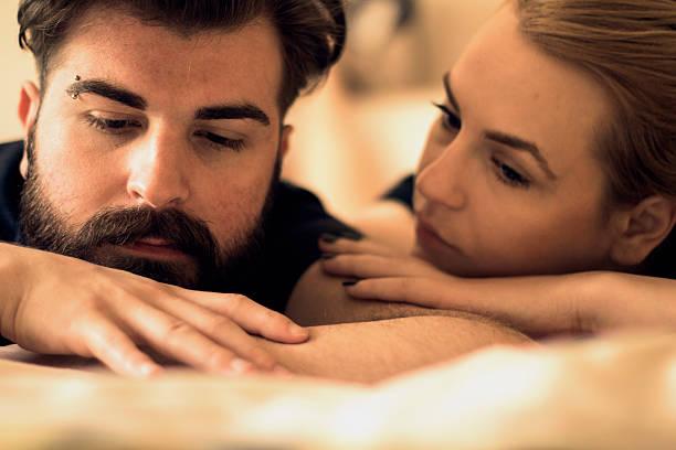Unhappy young heterosexual couple in bedroom - foto de acervo