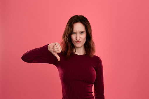 istock Unhappy young lady standing isolated over dark pink background with a gesture of thumb down symboling negative appraisal. 1158855039