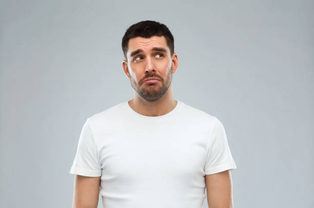 unglücklicher junger Mann über grauem Hintergrund – Foto