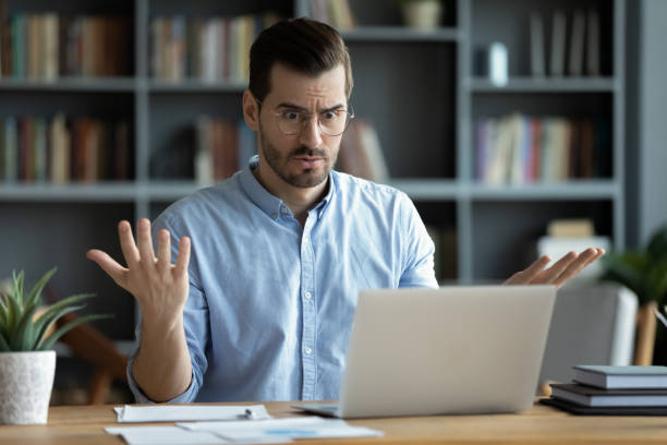Unhappy young man work on laptop confused by gadget problems stock photo