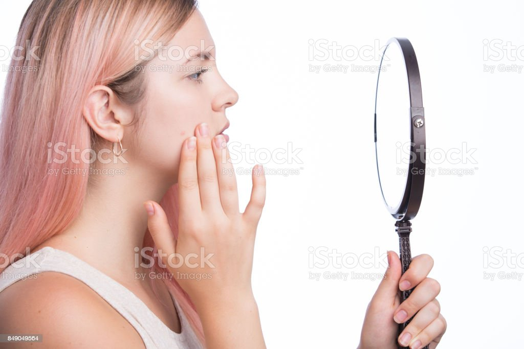 Unhappy young pretty girl looking at her pimple on her face in the mirror stock photo