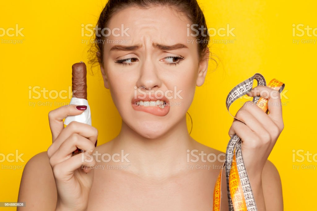 Unhappy young woman holding chocolate and metering tape on yellow background royalty-free stock photo