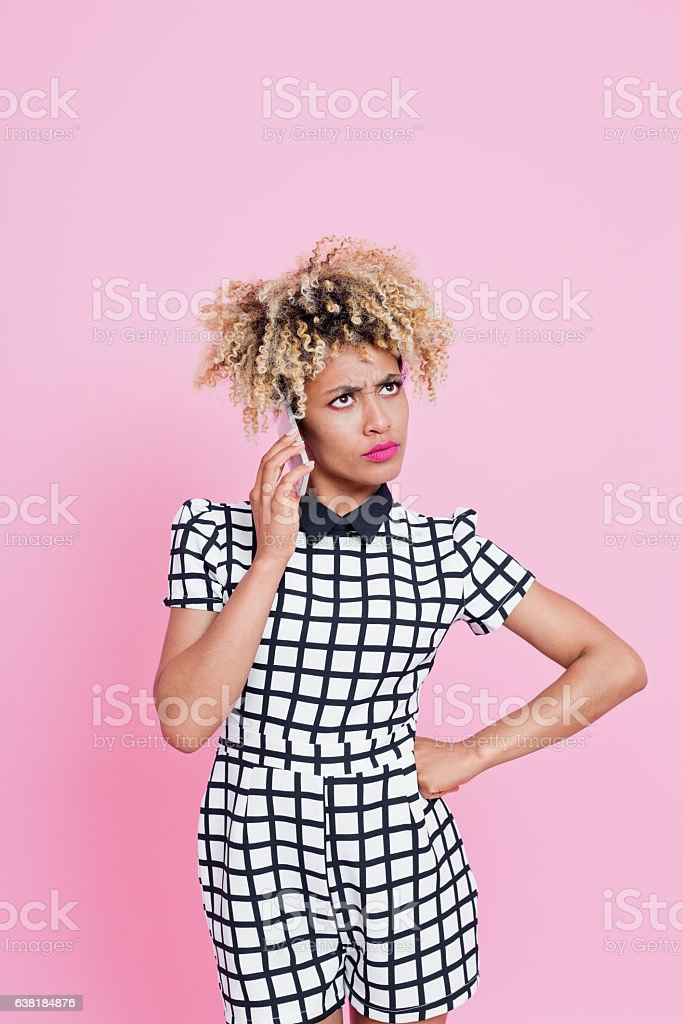 Unhappy Young Woman on her Phone Portrait of unhappy looking afro american woman calling support, waiting on her mobile or being annoyed by her conversation. She is wearing grid check playsuit. Studio shot, pink background. 25-29 Years Stock Photo