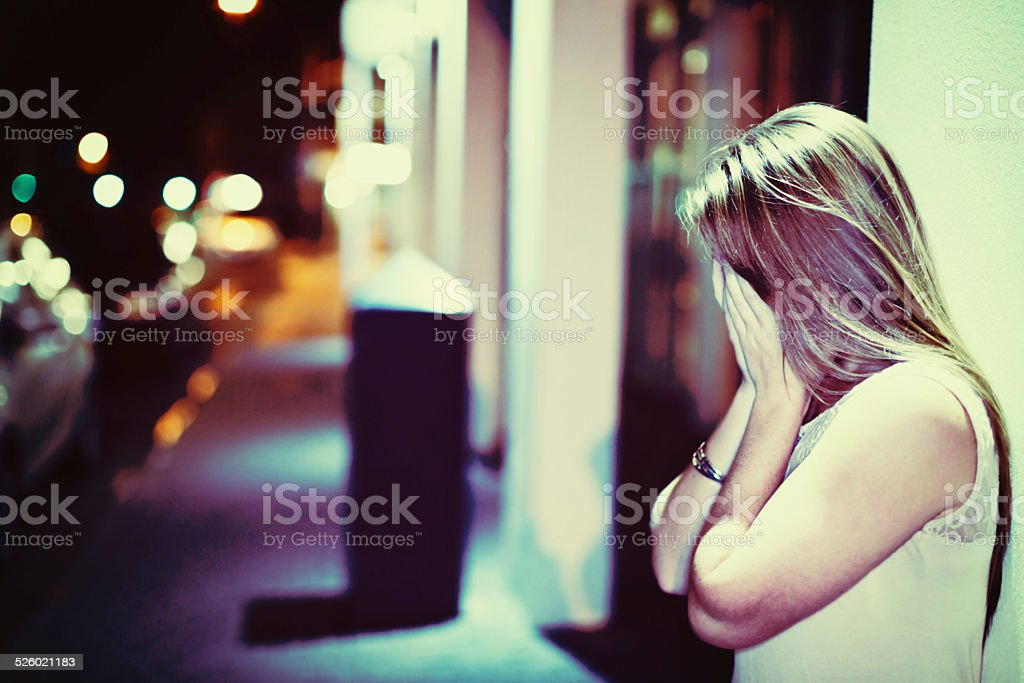 Unhappy young woman on nighttime street covers face with hands stock photo