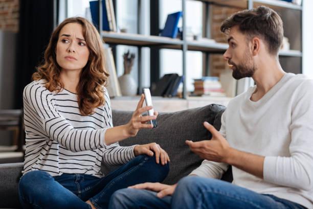 unglückliche junge frau zeigt eine telefon zu ihrem freund - liebesbeweis für ihn stock-fotos und bilder