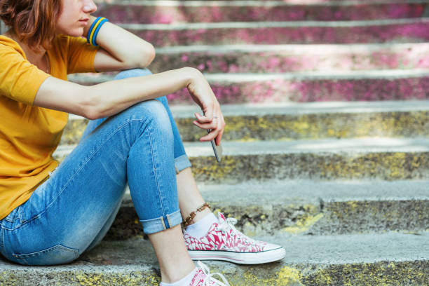 Unhappy young woman waiting outdoors on the stairs stock photo