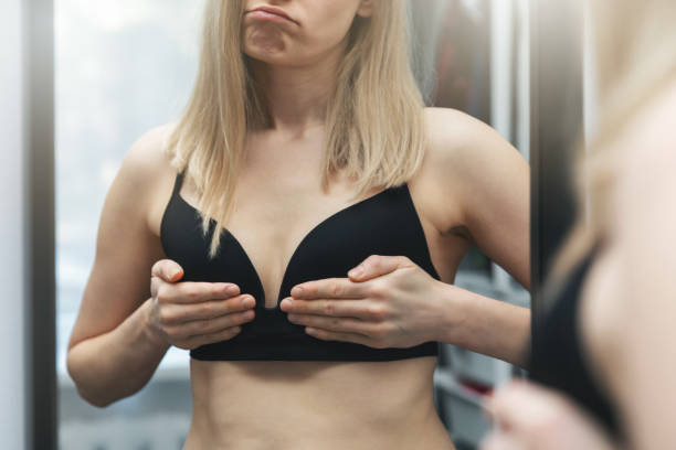 unhappy young woman wearing black bra checking her breasts in front of the mirror stock photo