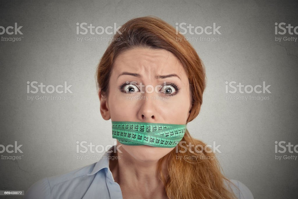 unhappy young woman with green measuring tape covering mouth stock photo