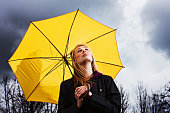 A beautiful young blonde woman sheltering under a sunny yellow umbrella looks up miserably as she waits for a thunderstorm to pass.