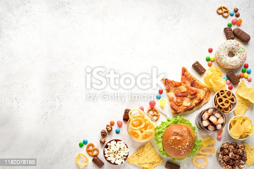 Assortment of Unhealthy Food on white, top view, copy space. Unhealthy eating, junk food concept.
