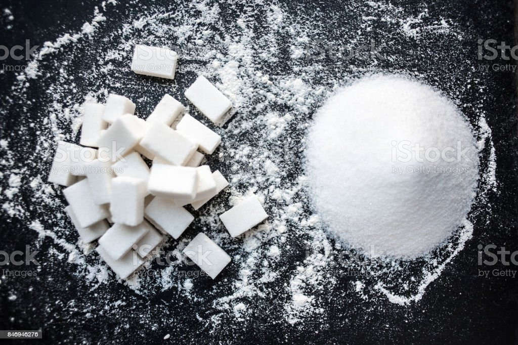 Unhealthy food concept - sugar  and flour on a black background. Dangerous high amount of sugar in food. Carbohydrates sources, top view'n stock photo